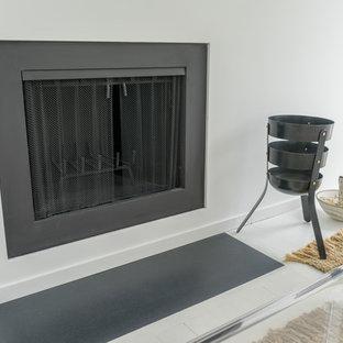 ニューヨークのモダンスタイルのおしゃれなLDK (フォーマル、白い壁、トラバーチンの床、標準型暖炉、金属の暖炉まわり、壁掛け型テレビ、白い床) の写真