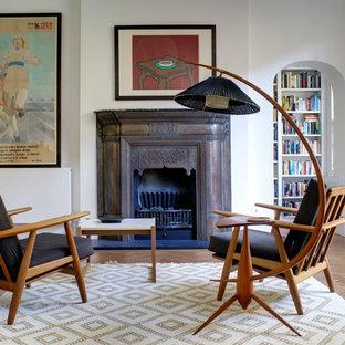 Réalisation d'un salon avec une bibliothèque ou un coin lecture vintage de taille moyenne et ouvert avec un mur blanc, un sol en bois brun, une cheminée standard, un manteau de cheminée en métal et aucun téléviseur.