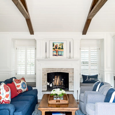 Living room - mid-sized traditional formal and open concept exposed beam and wainscoting living room idea in Los Angeles with white walls, a standard fireplace, a stone fireplace and no tv
