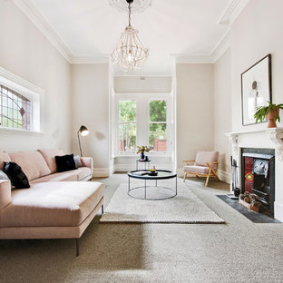 This is an example of a scandinavian formal enclosed living room in Adelaide with beige walls, carpet, a standard fireplace and grey floor.