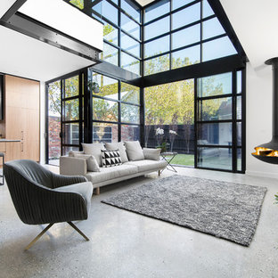 This is an example of a contemporary open concept living room in Melbourne with white walls and a hanging fireplace.