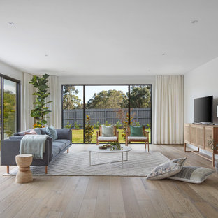 Inspiration for a contemporary living room in Melbourne with white walls, light hardwood floors, a freestanding tv and brown floor.