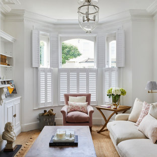 This is an example of a traditional enclosed living room in London with white walls, medium hardwood flooring, a standard fireplace, a wall mounted tv and brown floors.