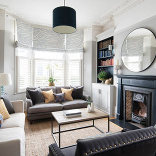 Inspiration for a victorian living room in London with a reading nook, grey walls, a wood burning stove and a tiled fireplace surround.