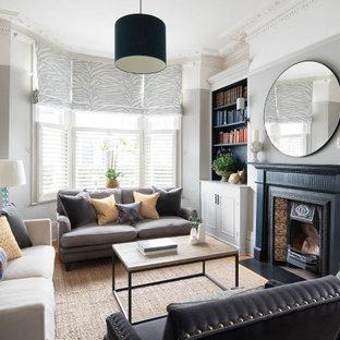 Cette image montre un salon avec une bibliothèque ou un coin lecture victorien avec un mur gris, un poêle à bois et un manteau de cheminée en carrelage.