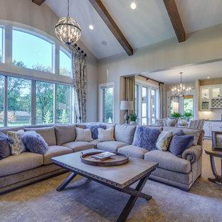 Ispirazione per un grande soggiorno american style aperto con pareti beige, pavimento in legno massello medio, camino classico, cornice del camino in pietra e parete attrezzata