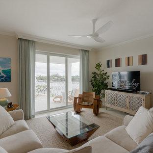 マイアミの中サイズのビーチスタイルのおしゃれなLDK (ベージュの壁、セラミックタイルの床、暖炉なし、据え置き型テレビ) の写真