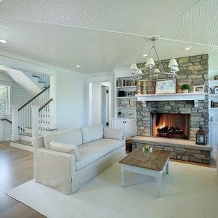 他の地域の小さいカントリー風おしゃれなLDK (グレーの壁、淡色無垢フローリング、標準型暖炉、石材の暖炉まわり、テレビなし、茶色い床) の写真