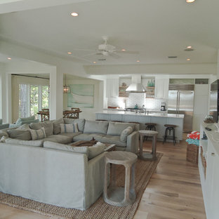 Small beach style open concept living room in Miami with white walls, light hardwood floors, no fireplace and a wall-mounted tv.