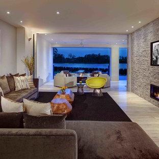 Geräumiges Modernes Wohnzimmer mit Gaskamin, Kaminumrandung aus Stein und Wand-TV in Orlando