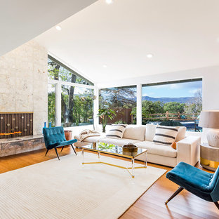 Mid-sized 1960s formal and open concept medium tone wood floor living room photo in Los Angeles with white walls, no tv, a standard fireplace and a stone fireplace