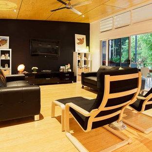 Ispirazione per un soggiorno moderno di medie dimensioni e aperto con pareti nere, pavimento in bambù e TV a parete