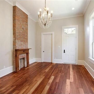 Living room - mid-sized craftsman formal and enclosed dark wood floor living room idea in New Orleans with beige walls, a standard fireplace, a brick fireplace and no tv