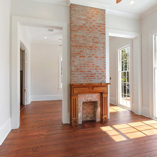 Inspiration for a mid-sized timeless formal and enclosed dark wood floor living room remodel in New Orleans with beige walls, a standard fireplace, a brick fireplace and no tv
