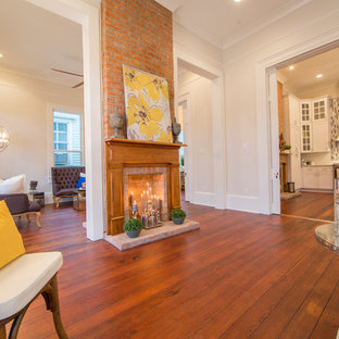 Example of a mid-sized transitional formal and open concept dark wood floor living room design in New Orleans with white walls, a standard fireplace, a wood fireplace surround and no tv