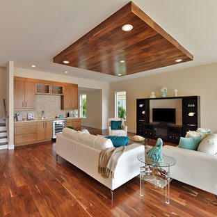 Living room - large beach style open concept medium tone wood floor living room idea in Tampa with beige walls and a media wall