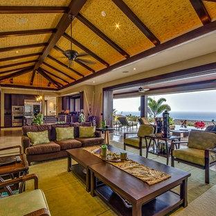 ハワイの巨大なトロピカルスタイルのおしゃれなLDK (ベージュの壁、トラバーチンの床、暖炉なし、埋込式メディアウォール) の写真