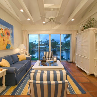 Photo of a coastal living room in Miami with terracotta flooring and a concealed tv.