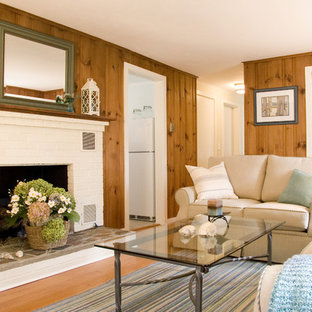 Inspiration for a mid-sized timeless enclosed medium tone wood floor living room remodel in Boston with brown walls, a standard fireplace and a brick fireplace