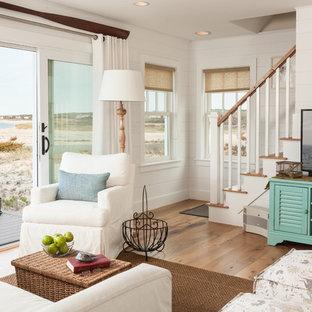 Ejemplo de salón costero con paredes blancas, televisor independiente y suelo de madera clara