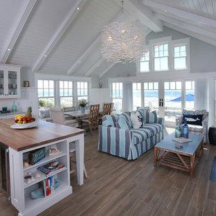 小さいビーチスタイルのおしゃれなリビングロフト (青い壁、無垢フローリング、茶色い床) の写真