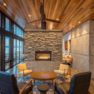 Ejemplo de salón abierto, moderno, pequeño, sin televisor, con paredes grises, suelo de baldosas de porcelana, chimenea de doble cara, marco de chimenea de piedra y suelo beige