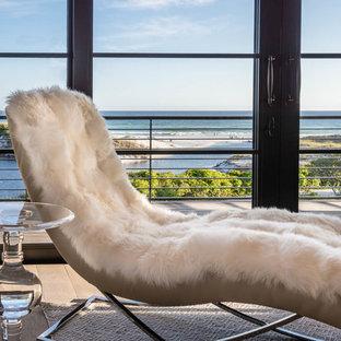 マイアミの中サイズのビーチスタイルのおしゃれなLDK (フォーマル、白い壁、無垢フローリング、標準型暖炉、コンクリートの暖炉まわり、テレビなし、茶色い床) の写真