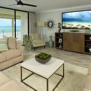 オーランドの広いビーチスタイルのおしゃれなLDK (グレーの壁、淡色無垢フローリング、壁掛け型テレビ、白い床) の写真