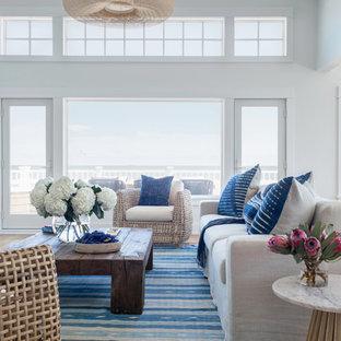 ニューヨークの広いビーチスタイルのおしゃれなLDK (白い壁、無垢フローリング、標準型暖炉、レンガの暖炉まわり、壁掛け型テレビ、茶色い床) の写真