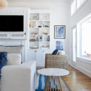ニューヨークの大きいビーチスタイルのおしゃれなLDK (白い壁、無垢フローリング、標準型暖炉、レンガの暖炉まわり、壁掛け型テレビ、茶色い床) の写真