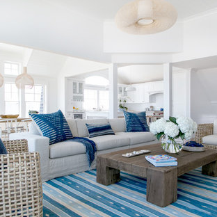 Living room - beach style open concept medium tone wood floor and brown floor living room idea in New York with white walls