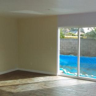 オレンジカウンティの小さいビーチスタイルのおしゃれなLDK (黄色い壁、セラミックタイルの床、暖炉なし、茶色い床) の写真