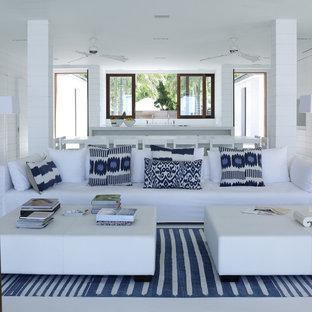 Immagine di un ampio soggiorno tropicale con sala formale, pareti bianche, pavimento in cemento, nessun camino e nessuna TV
