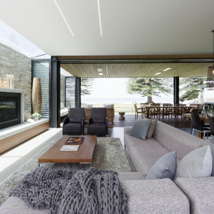 Inspiration for a mid-sized contemporary open concept living room in Central Coast with grey walls, concrete floors, a standard fireplace, a concrete fireplace surround, a built-in media wall and grey floor.