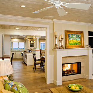 This is an example of a mid-sized beach style open concept living room in Los Angeles with yellow walls, light hardwood floors, a two-sided fireplace, a stone fireplace surround and a wall-mounted tv.