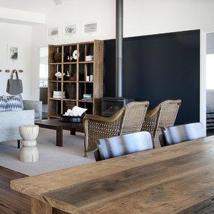 シドニーの中サイズのビーチスタイルのおしゃれなLDK (黒い壁、濃色無垢フローリング、薪ストーブ、金属の暖炉まわり、テレビなし、茶色い床) の写真