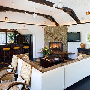 Esempio di un soggiorno stile marinaro aperto con angolo bar, camino ad angolo, cornice del camino in pietra e TV a parete