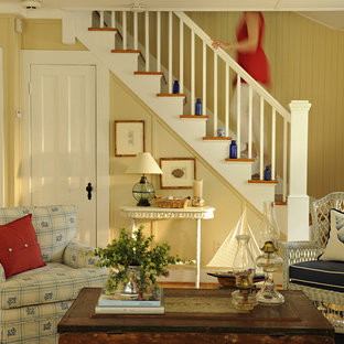 This is an example of a medium sized nautical formal open plan living room in New York with yellow walls, medium hardwood flooring and no fireplace.