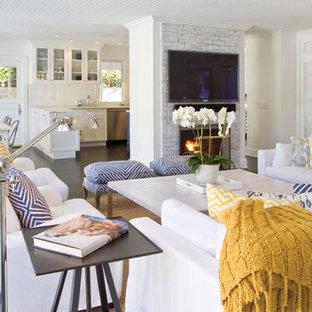 ニューヨークの巨大なビーチスタイルのおしゃれなLDK (フォーマル、白い壁、濃色無垢フローリング、標準型暖炉、レンガの暖炉まわり、壁掛け型テレビ) の写真