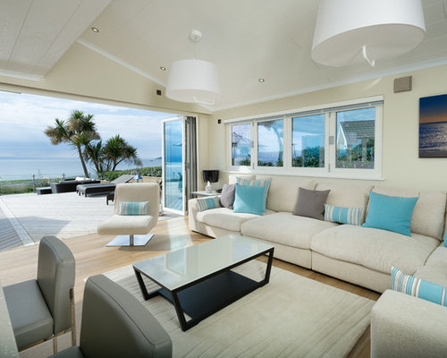 Example Of A Coastal Formal And Open Concept Light Wood Floor And Beige  Floor Living Room
