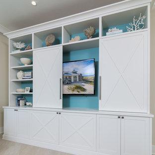 Ejemplo de salón abierto, marinero, grande, con paredes beige, suelo de piedra caliza y pared multimedia