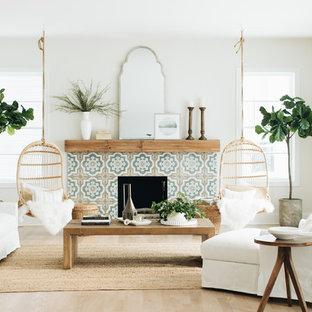 Ejemplo de salón para visitas costero, sin televisor, con paredes blancas, suelo de madera clara, chimenea tradicional, marco de chimenea de baldosas y/o azulejos y suelo beige