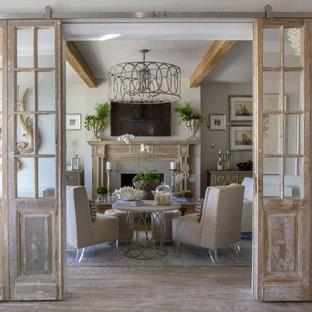 Immagine di un soggiorno shabby-chic style chiuso con pareti grigie, parquet chiaro, camino classico e TV a parete