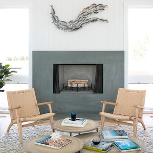 Example of a beach style light wood floor living room design in New York with white walls, a standard fireplace and a concrete fireplace