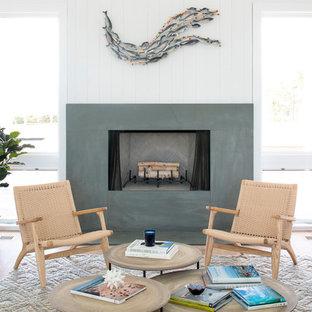 ニューヨークのビーチスタイルのおしゃれなリビング (白い壁、淡色無垢フローリング、標準型暖炉、コンクリートの暖炉まわり) の写真