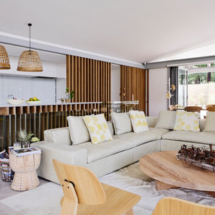 Photo of a beach style open concept living room in Sydney with white walls and grey floor.