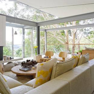 Diseño de salón abierto, costero, de tamaño medio, con paredes blancas, suelo de cemento, chimenea tradicional, marco de chimenea de metal y suelo gris