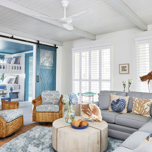 Example of a beach style medium tone wood floor and brown floor living room design in Other with white walls