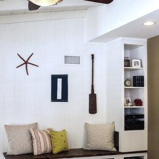 サンディエゴの中サイズのビーチスタイルのおしゃれなLDK (マルチカラーの壁、カーペット敷き、標準型暖炉、壁掛け型テレビ) の写真