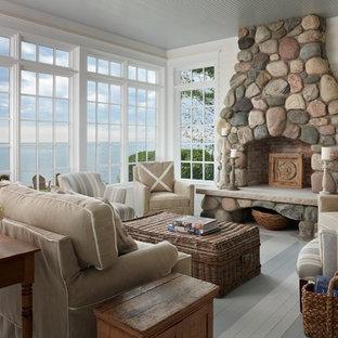 Foto på ett mellanstort maritimt separat vardagsrum, med vita väggar, målat trägolv, en standard öppen spis och en spiselkrans i sten